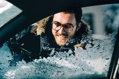 Nahes hohes Porträt des Mannes unter Verwendung des Schabers für von Autofenstern heraus säubern Wintertransport und Fahrzeugkonz stockfotos