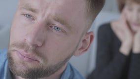 Nahes hohes Porträt des traurigen unglücklichen jungen Mannes, der weg im Vordergrund schaut Die unscharfe Zahl reifer Dame sie h stock footage