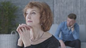 Nahes hohes Porträt einer älteren reifen Frau, die in der Kamera im Vordergrund schaut Die unscharfe Zahl vom traurigen stock video