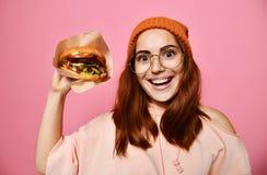 Nahes hohes Porträt einer hungrigen jungen Frau, die den Burger lokalisiert über rosa Hintergrund isst stockbilder