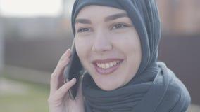 Nahes hohes Porträt einer jungen schönen moslemischen Frau im schwarzen Kopfschmuck oben sprechend durch Handyabschluß Nettes asi stock video footage