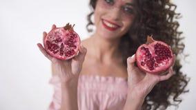 Nahes hohes Porträt eines recht lächelnden jungen gelockten Mädchens, das zwei Hälften eines saftigen Granatapfels hält Langsame  stock footage