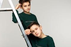 Nahes hohes Porträt von Bruderjugendlichen in den grünen Strickjacken stockfoto