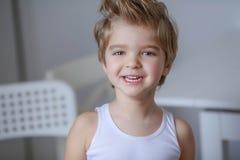 Nahes hohes Porträt von nettem, entzückend, tragender Denimoverall des Kleinkindjungen, langes T-Shirt, sitzend auf dem Boden und lizenzfreie stockfotografie