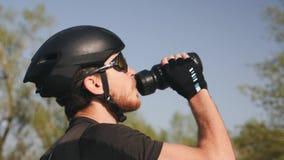 Nahes hohes Porträt von triathlete im schwarzen Sturzhelm und in Trinkwasser der Gläser Bärtiger männlicher Radfahrer trinkt Wass stock video