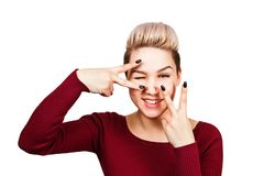 Nahes hohes Portr?t der jungen gl?cklichen L?chelnfrau im roten Kleidershowsieg, Positiv, Friedenszeichen auf ihrem Auge Lokalisi lizenzfreie stockfotos