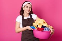 Nahes hohes Studioporträt der netten lächelnden netten Frau, die rosa Becken mit Wäscherei in beiden Händen hat, schaut positiv u stockfoto