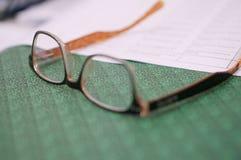 Nahes Notizbuch, öffnen ein Blatt und Gläser auf dem Bürotisch am Arbeitsplatz lizenzfreie stockbilder