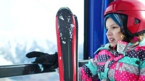 Nahes Porträt auf dem Hintergrund von schneebedeckten Bergen Mädchenjugendlicher in einem Sturzhelm und mit Skis klettert einen B stock video footage