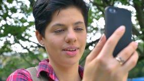 Nahes Porträt der jungen hübschen Frau, die Videochat hat und, stehend in der Parktageszeit lächelt stock video footage