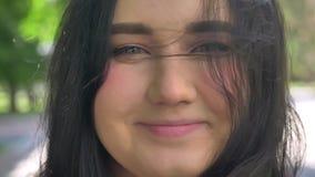 Nahes Porträt der schönen überladenen Brunettefrau, die Kamera, sonniges Wetter im Park lächelt und betrachtet stock video footage