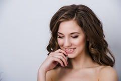 Nahes Porträt der schönen lächelnden Brautfrau mit dem langen gelockten Haar, das im Hochzeitskleid am Innenraum und am Lächeln a Lizenzfreie Stockfotos