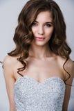 Nahes Porträt der schönen lächelnden Brautfrau mit dem langen gelockten Haar, das im Hochzeitskleid am Innenraum und am Lächeln a Lizenzfreie Stockbilder