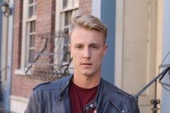 Nahes Porträt des hübschen erwachsenen blonden Mannes, mit blured städtischem klassischem Hintergrund Stockbild