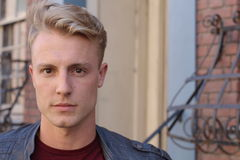 Nahes Porträt des hübschen erwachsenen blonden Mannes, mit blured städtischem klassischem Hintergrund Lizenzfreies Stockfoto