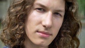 Nahes Porträt des jungen ernsten gutaussehenden Mannes mit dem langen gelockten Haar, das Kamera, Konzentration und Bestimmung be stock video footage