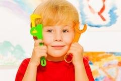 Nahes Porträt des Jungen mit Arbeitsspielzeugwerkzeugen Stockbilder