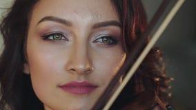 Nahes Porträt des schönen weiblichen Violinisten, der den Geigenbogen auf Schnur beeinflußt stock video