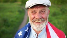 Nahes Porträt eines amerikanischen Landwirts mit einer Flagge auf seinen Schultern am 4. Juli, USA-Unabhängigkeitstagfeiertag A stock video footage