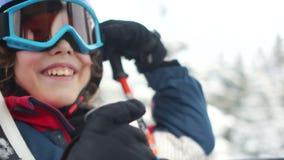 Nahes Porträt eines Jugendlichjungen in einem Sturzhelm und der Schutzbrillen in einer Skiaufzugkabine Skiort, glücklicher Famili stock video