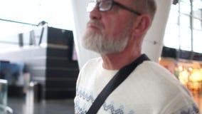 Nahes Porträt eines reifen Mannes mit einem grauen Bart und der Gläser am Flughafen Der Pensionär betrachtet oben dem Flug stock video footage