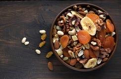 Nahrhafte Trockenfrüchte und Nüsse in der Schüssel auf hölzernem Hintergrund Lizenzfreie Stockfotos