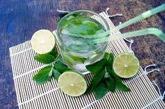 Nahrhaftes Detoxwasser mit Kalk und Minze in einem Glas auf dem hölzernen Hintergrund Stockfotos