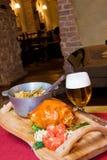 Nahrung auf hölzernem Tellersegment und Bier Stockfoto