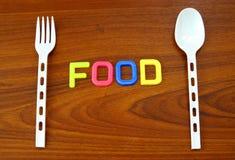 Nahrung in den bunten Zeichen mit Löffel und Gabel Stockfoto