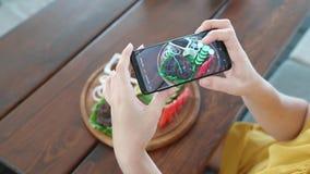 Nahrungbloggerhände unter Verwendung des Smartphone, der Foto des schönen Rindfleischsteaks auf hölzerner Tabelle macht stock footage