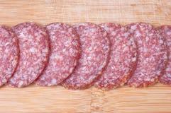 Nahrungsmittelhintergrund der geschnittenen Salami Stockfotografie