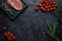 Nahrungsmittelhintergrund mit Exemplar-Platz Rohes Rippenaugensteak mit Tomaten und Rosmarin auf Draufsicht des schwarzen Hinterg lizenzfreie stockfotos