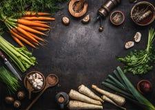 Nahrungsmittelhintergrund mit verschiedenem Biohofgem?se auf dunkler rustikaler Tabelle mit K?chenger?ten, Kr?utern und Gew?rzen, lizenzfreies stockfoto