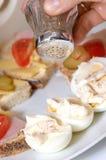 Nahrungsmittelplatte und sich setzen Salz auf Eiern Lizenzfreies Stockbild