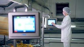 Nahrungspflanzearbeitskraft steuert einen Förderer, der von den Kartoffelchips voll ist stock video footage