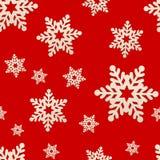 Nahtlose Beschaffenheit von hölzernen Schneeflocken auf einem roten Hintergrund Stockfoto