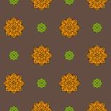 Nahtloses Muster mit den orange und grünen ethnischen Rosetten auf einem braunen Hintergrund Stockfotografie