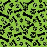 Nahtloses Muster mit den schwarzer Hundepfotenabdrücken und -knochen auf einem grünen Hintergrund Stockbild