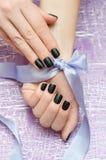 Nail art. Beautiful female hand with black matte manicure Stock Image