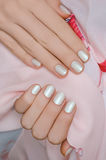 Nail art. Beautiful female hand with white manicure Royalty Free Stock Images
