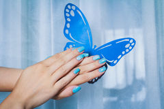 Nail art with blue background and white lace. With blue butterfly Royalty Free Stock Photo