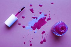 Neil polish drops spilled near the glass bottle and tassel. Nail art concept in modern neon colors royalty free stock photos