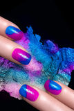 Nail Art. Fluor Nail Polish and Mineral Colorful Eye Shadow. Nail Art. Fingers with luxury nails and crushed eye shadow with drops of water. Manicure and makeup royalty free stock photography