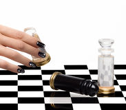 Nail Art. Manicure and Chess. Beautiful woman hand with luxury nails in black and white playing chess. Manicure and nail art concept. Closeup portrait isolated Stock Photos