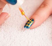 Nail art - painting gold stripes on dark blue base polish Stock Images