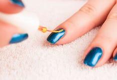 Nail art - painting gold stripes on dark blue base polish stock photo