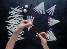 Nail art samples in female hands on the black table. stock photography