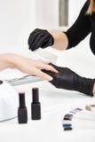 Nail artist shortening nails doing manicure at salon. Manicure set. Stock Image