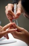 Nail beautician polishing nails Royalty Free Stock Images