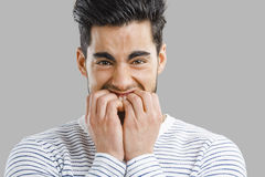 Nail Biting. Close-up portrait of a worried young man biting nails royalty free stock photos